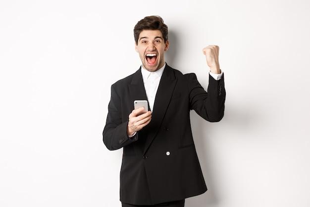 Retrato de feliz homem bonito de terno, regozijando-se, atingir a meta no aplicativo móvel, levantando o punho e gritando sim, segurando o smartphone, em pé contra um fundo branco