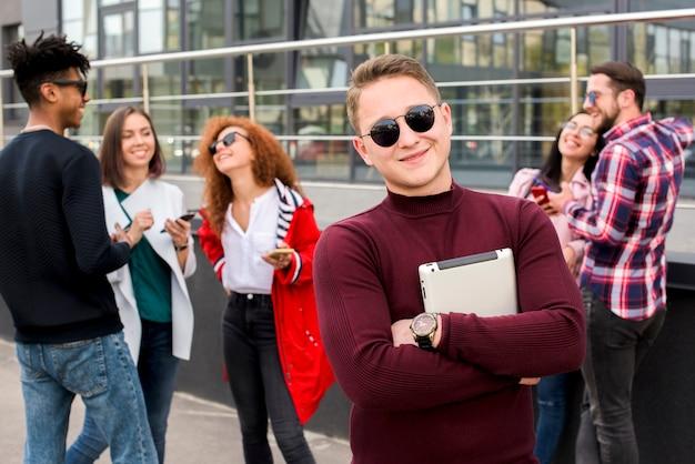 Retrato, de, feliz, homem jovem, carregar, tablete digital, olhando câmera