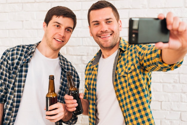 Retrato, de, feliz, homem jovem, segurando, garrafa cerveja, em, mão, levando, selfie, com, seu, amigos, ligado, smartphone