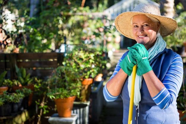 Retrato de feliz jardineiro maduro no jardim