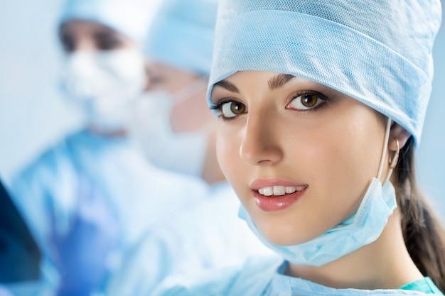 Retrato de feliz jovem cirurgiã ou estagiária após uma operação bem-sucedida com seus colegas operando