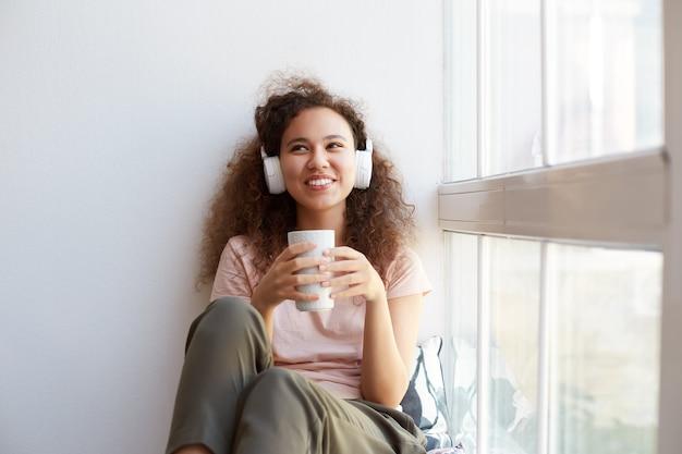 Retrato de feliz jovem mulata encaracolada sentada perto da janela, bebendo chá, ouvindo música favorita em fones de ouvido e aproveitando o dia ensolarado em casa.