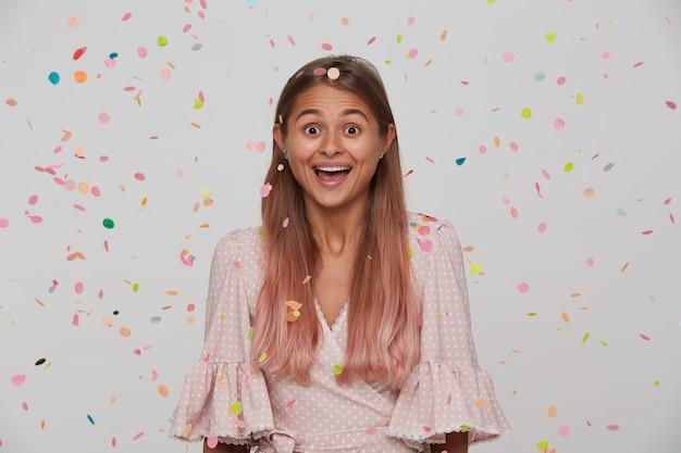 Retrato de feliz linda jovem de cabelos compridos regozijando-se com sua festa de aniversário, sendo surpreendida com seus amigos e sorrindo alegremente, isolada sobre uma parede branca