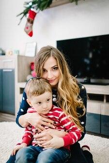 Retrato de feliz mãe e filho celebram o natal. feriados de ano novo. criança com a mãe no quarto festivamente decorado com árvore de natal e enfeites.