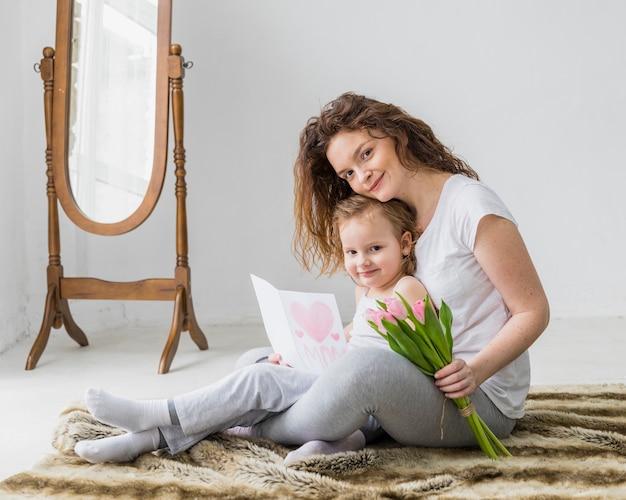Retrato, de, feliz, mãe filha, com, cartão, e, tulipa, flores, olhando câmera