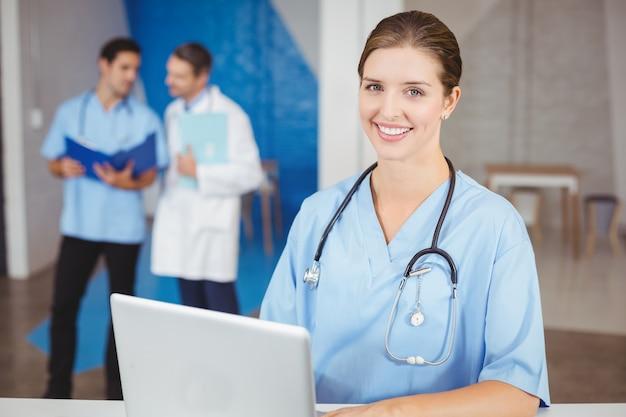 Retrato de feliz médico feminino com laptop