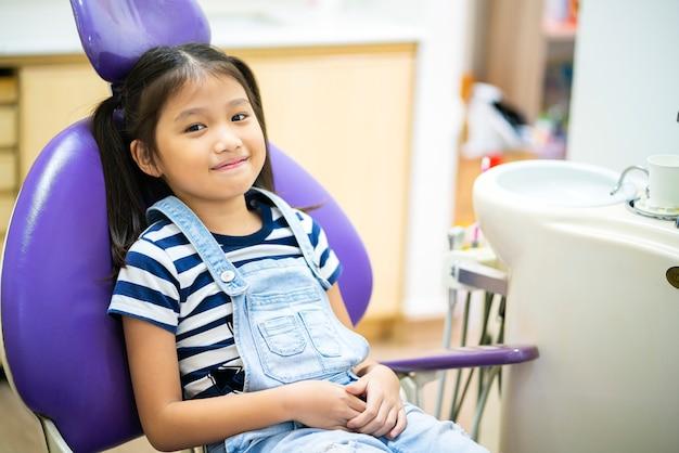Retrato de feliz menina asiática no consultório dental. conceitos de cuidados dentários, cuidados médicos, estilo de vida, clínica dentária ou procedimento dentário