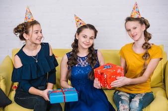 Retrato, de, feliz, meninas adolescentes, sentando, ligado, amarela, sofá, com, dela, amigos, segurando, presentes