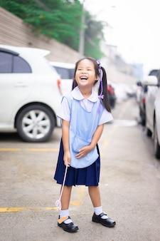 Retrato, de, feliz, menininha, em, tailandês, uniforme escola, ficar, parque estacionamento, pronto, costas, para, escola