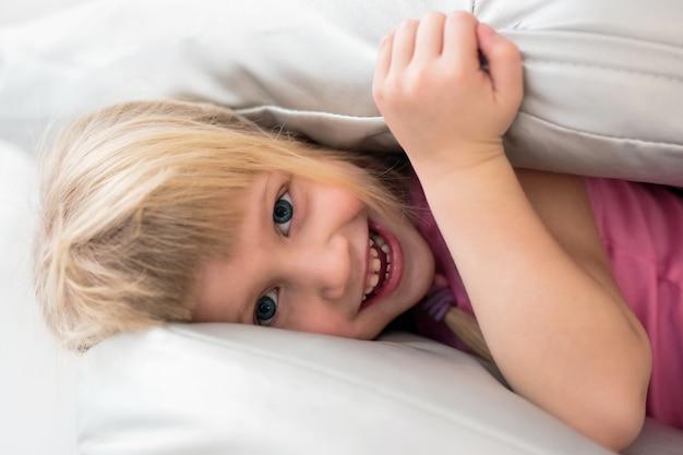 Retrato, de, feliz, menininha, tocando, com, travesseiros, cama