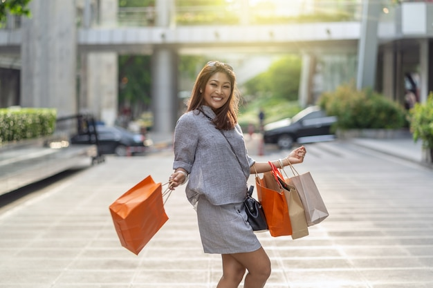 Retrato, de, feliz, mulher asian, andar, e, segurando, a, bolsa de compra, em, centro cidade