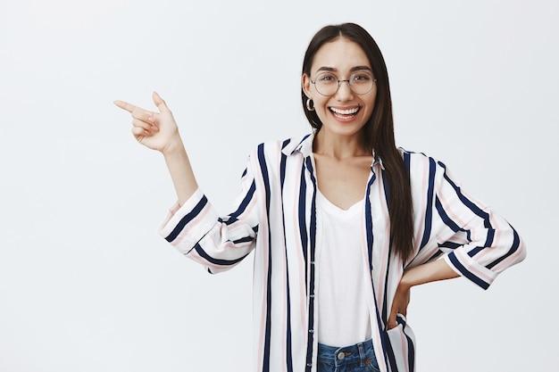Retrato de feliz mulher de negócios bonita em brincos e óculos, segurando a mão no quadril e mostrando a esquerda