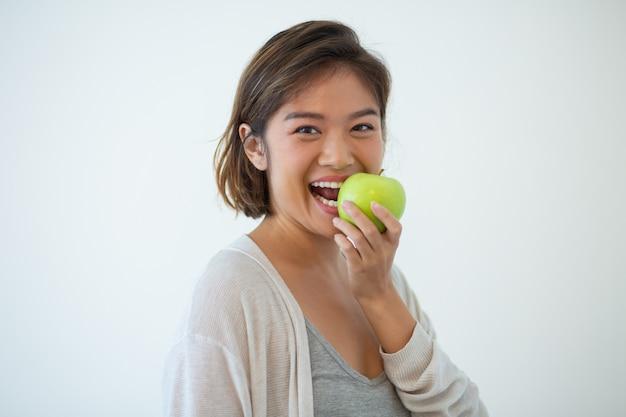 Retrato, de, feliz, mulher jovem, morder, maçã