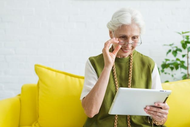 Retrato, de, feliz, mulher sênior, olhar, em, tablete digital