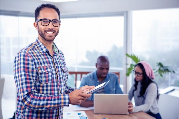 Retrato, de, feliz, mulheres negócios, usando, tablete digital, enquanto, ficar, em, escritório