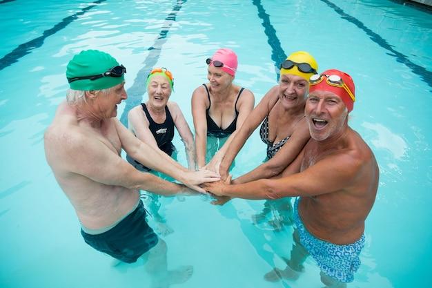 Retrato de feliz nadador sênior empilhando as mãos na piscina