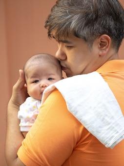 Retrato, de, feliz, pai asian, segurando, seu, bebê doce recém-nascido, vestido, em, branca, roupas