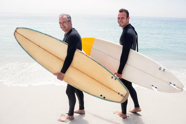 Retrato de feliz pai e filho em roupa de mergulho segurando uma prancha de surf