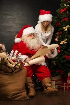 Retrato de feliz papai noel com seu ajudante lendo carta de natal ou lista de desejos