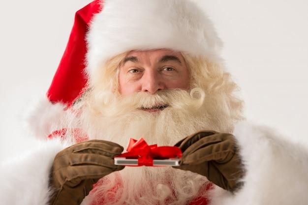 Retrato de feliz papai noel segurando dispositivo de presente nas mãos com fita