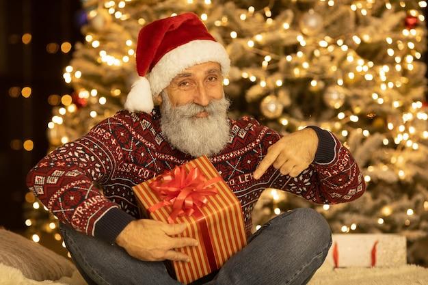 Retrato de feliz papai noel sentado em seu quarto em casa, perto de árvore de natal.