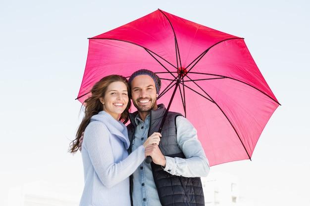 Retrato, de, feliz, par jovem, segurando, guarda-chuva rosa, junto, ao ar livre
