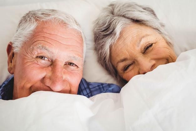 Retrato, de, feliz, par velho, sorrindo, enquanto, encontrar-se cama, em, quarto