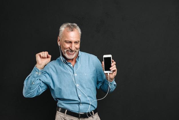 Retrato de feliz pensionista masculino dos anos 60 com cabelos grisalhos dançando enquanto ouve música através de fones de ouvido brancos usando telefone celular, isolado sobre a parede preta