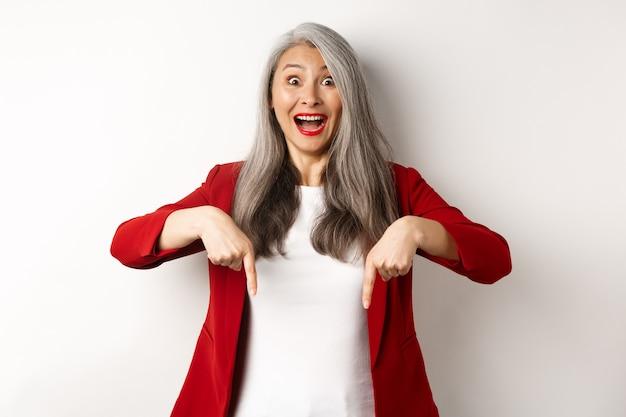 Retrato de feliz senhora asiática no blazer vermelho mostrando o logotipo, apontando os dedos para baixo e sorrindo alegre, veja este gesto, fundo branco.