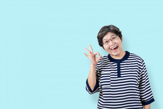 Retrato, de, feliz, sênior, mulher asian, gesto, ou, mostrando, mão, ok, e, olhando câmera