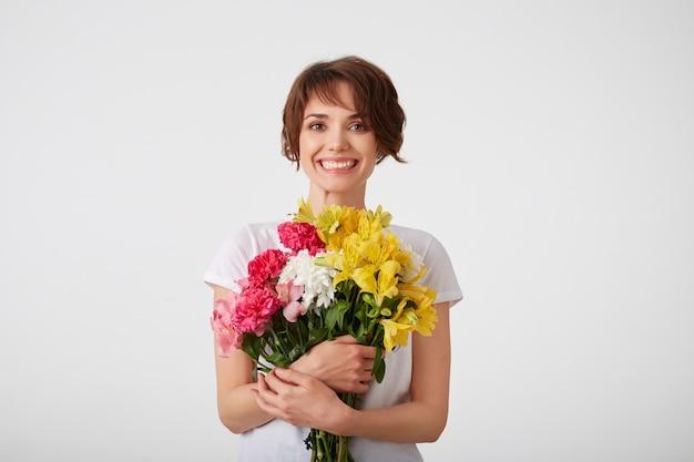 Retrato de feliz sorridente jovem bonita de cabelos curtos em t-shirt branca em branco, segurando um buquê de flores coloridas com os olhos fechados, em pé sobre um fundo branco.