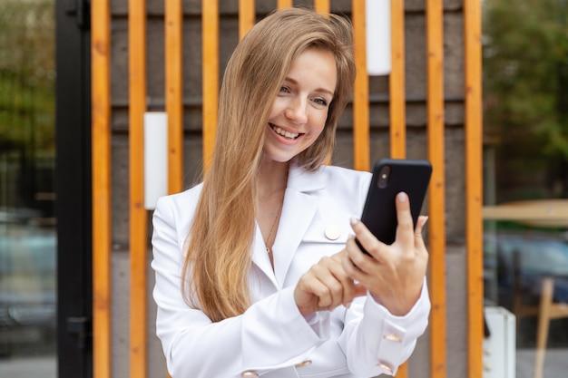 Retrato de feliz sorridente jovem empresária com cabelos longos, usando um smartphone
