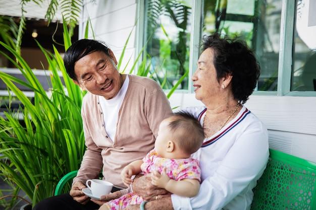 Retrato, de, feliz, sorrindo, avós asiáticos, e, bebê, neta, casa