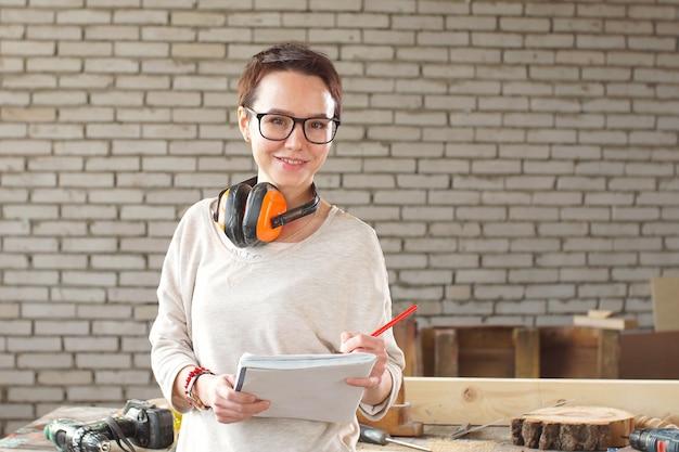 Retrato de feliz trabalhadora atraente em copos com caneta e tablet na oficina