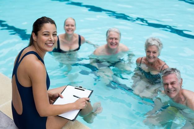 Retrato de feliz treinadora e nadadoras sênior