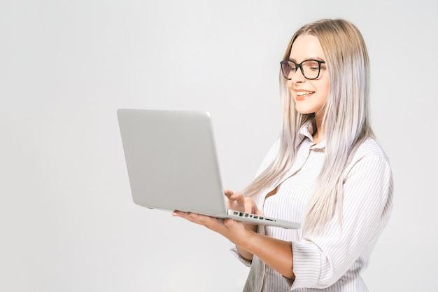 Retrato de feliz wow jovem linda mulher sorridente em pé com laptop isolado no fundo branco. espaço para texto.