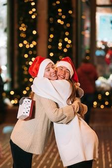 Retrato de felizes fofos jovens amigos abraçando uns aos outros e sorrindo enquanto caminhava ao ar livre na véspera de natal.