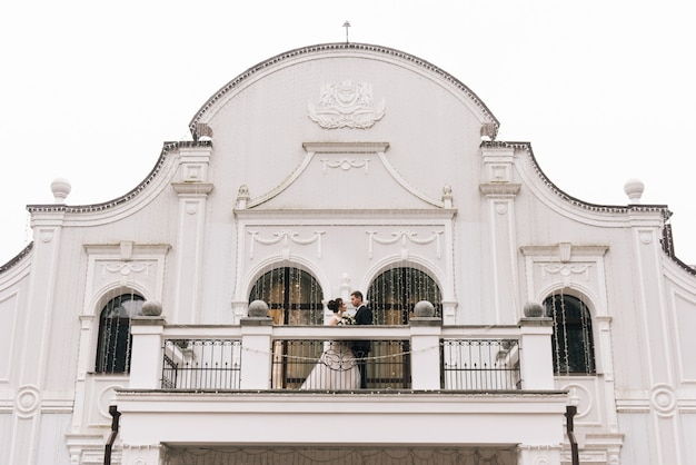 Retrato de felizes jovens amantes da noiva e do noivo na varanda de um lindo hotel. dia do casamento