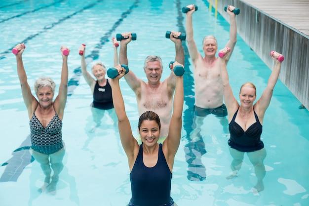 Retrato de felizes nadadores sênior com treinador durante o treinamento de levantamento de peso na piscina