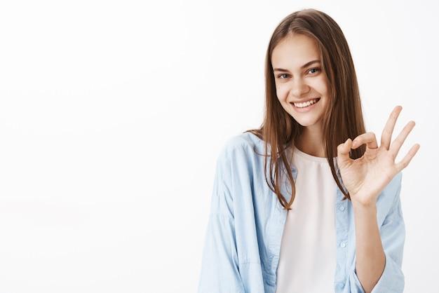 Retrato de feminina morena elegante, feliz e confiante em uma blusa azul da moda sobre uma camiseta branca, mostrando um gesto de ok ou ok e sorrindo com olhar seguro