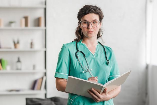 Retrato, de, femininas, enfermeira, segurando livro, e, caneta