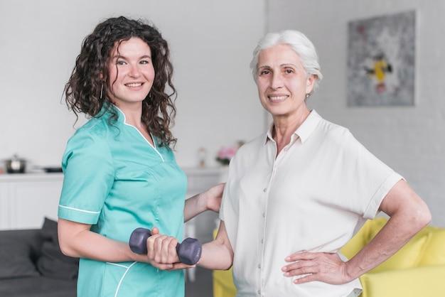Retrato, de, femininas, fisioterapeuta, e, mulher sênior, paciente, exercitar