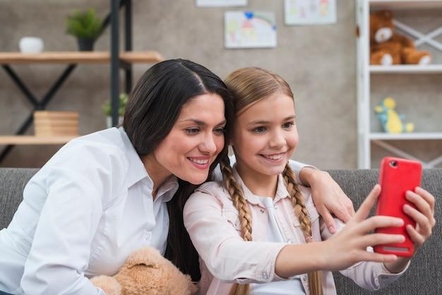 Retrato, de, femininas, psicólogo, e, menina, levando, selfie, de, telefone móvel