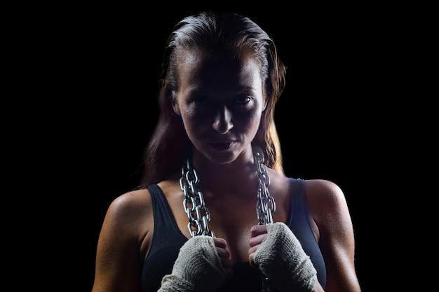 Retrato de feminino boxeador segurando corrente ao redor do pescoço