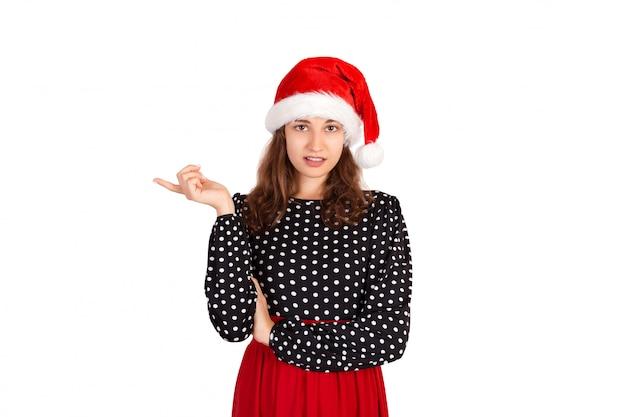 Retrato de feminino descontente gesticulando com o dedo no gesto de não ou de recusa. garota emocional no chapéu de natal papai noel isolado