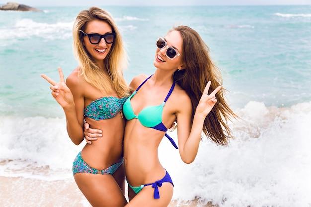 Retrato de férias de verão de duas meninas elegantes melhores amigas abraços e mostrando a ciência da peça, usando joias e biquínis sensuais elegantes, posando na praia de ilha paradisíaca.