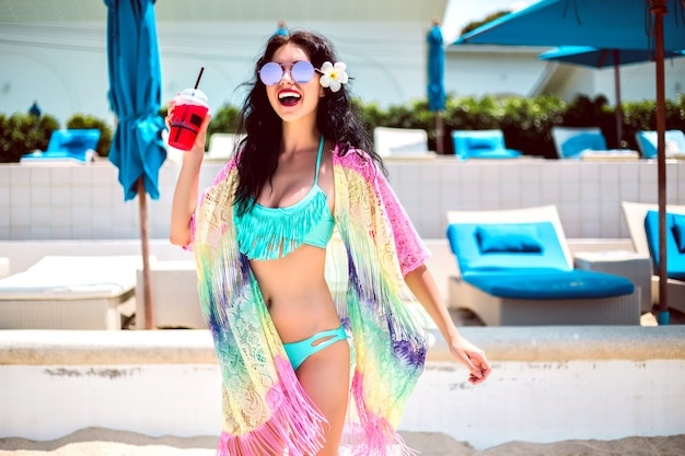 Retrato de férias positivo de verão de uma mulher bonita morena se divertindo no clube de praia de luxo, corpo magro, biquíni da moda e quimono, segurando um refrigerante.
