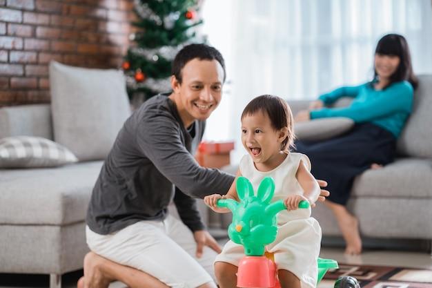 Retrato de filha brincando de triciclo com o pai ajudado e a mãe sentada em um sofá atrás
