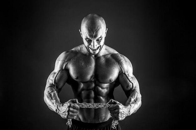 Retrato de fisiculturista agressivo tentando rasgar a corrente de metal
