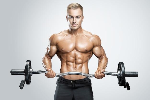 Retrato de fisiculturista bonito realizando a rosca direta de bíceps com barra de rosca direta na academia de físico perfeito ...